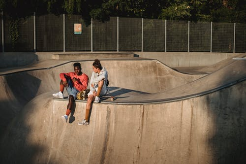 Young diverse male friends spending free time together while sitting with skateboards on ramp in skate park on summer sunny day