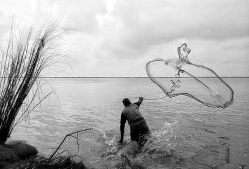 Man in Black Long Sleeve Shirt Holding a Fishing Net in Grayscale Photography