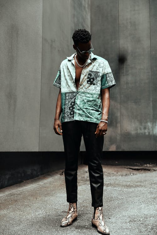 Stylish black man standing near concrete wall