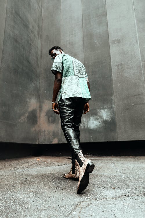Low angle back view emotionless African American male in trendy clothes stepping towards gray wall and looking at camera