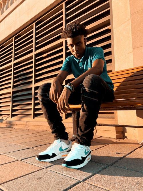 Serious black man sitting on street  bench