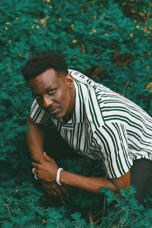 Emotionless black man hunkering on green lawn