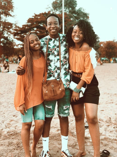 Happy young African American friends gathering together on sandy beach and embracing each other while looking at camera with toothy smiles