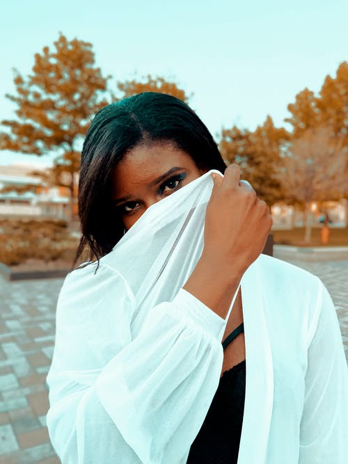 Calm young ethnic female covering half face with white jacket while standing in autumn park and looking at camera
