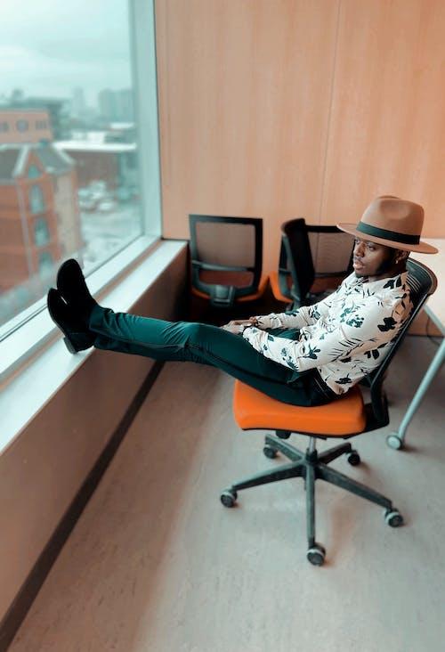 Stylish black man sitting on chair with legs on windowsill