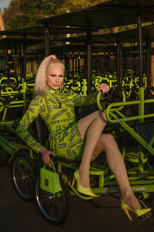 Woman in Green and Black Long Sleeve Dress Sitting on Green and Black Bicycle