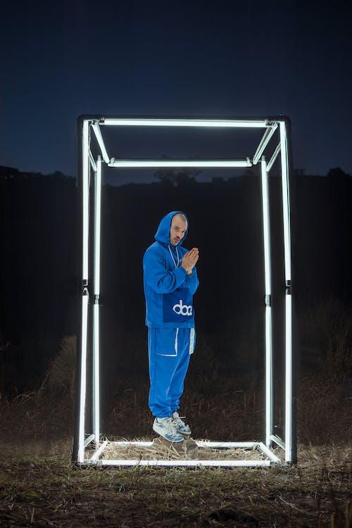 Man in Blue Hoodie Standing Beside White Metal Frame