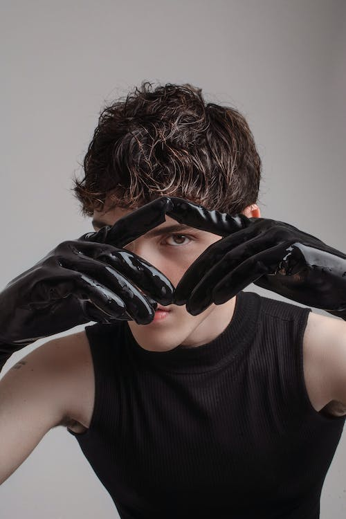 Woman in Black Tank Top Covering Face With Black Leather Gloves
