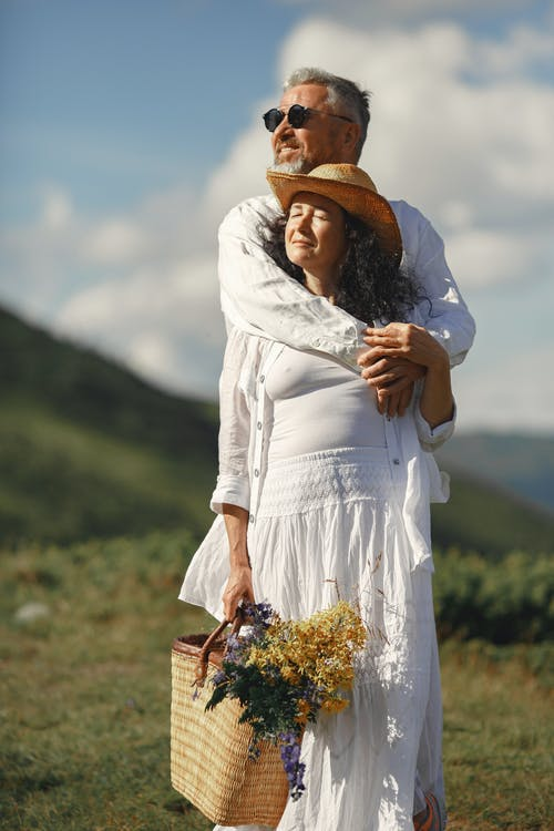 Man Hugging Woman in White Dress and Brown Hat Standing on Green Grass Field