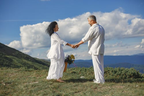 Man in White Dress Shirt and Woman in White Dress Holding Hands on Green Grass Field