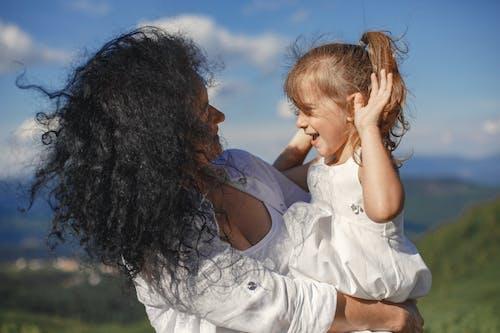 Woman Carrying a Cute Girl