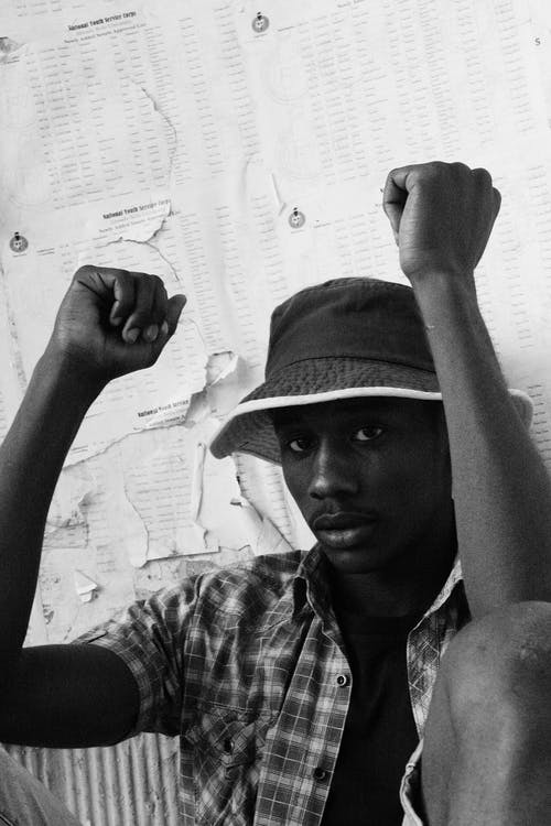 Attentive African man with raised arms near paper wall