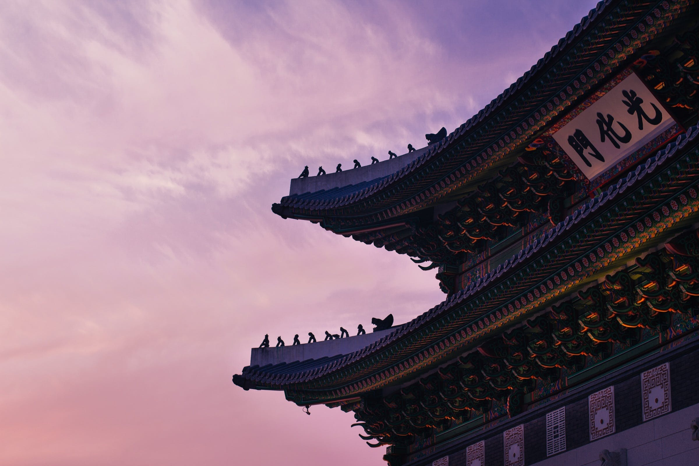 Chinese Temple With Kanji Banner on Top Under Orange and Purple Cloudy Sky