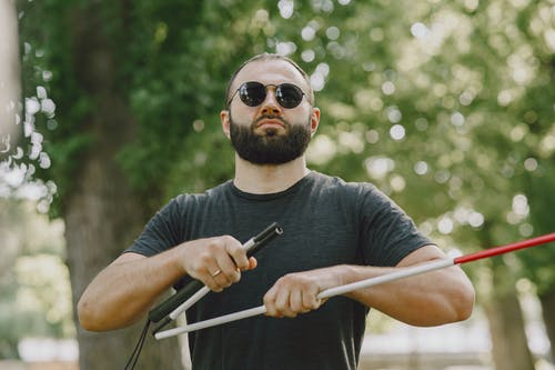 Man in Black Crew Neck T-shirt Wearing Black Sunglasses Holding White Cane