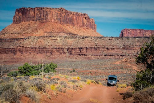 Van on Dirt Road with Butte in Background