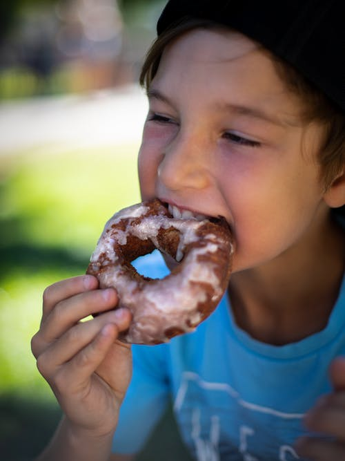 Boy in Blue Crew Neck Shirt Eating Doughnut