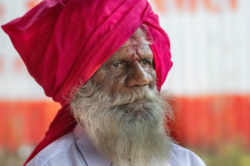 Thoughtful wise elderly Indian Sikh with beard in turban