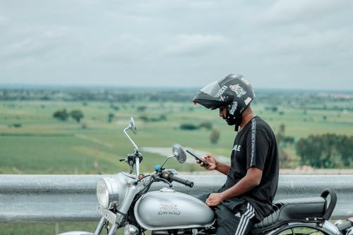 Male biker sitting on motorcycle with smartphone