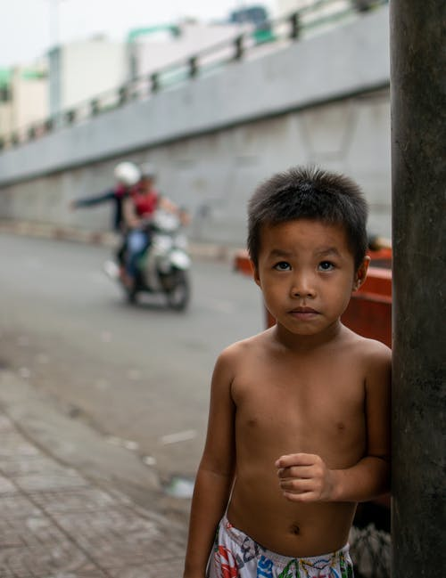 Shirtless Boy Leaning on a Street Post