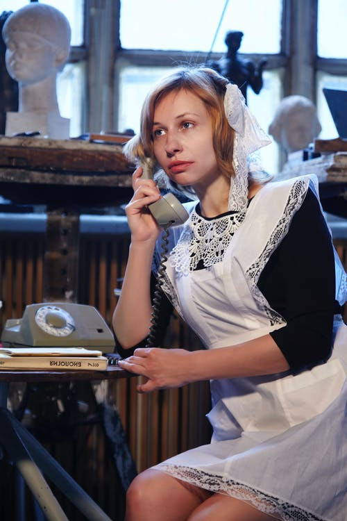 Pensive female wearing vintage school outfit speaking on landline phone while sitting at table in USSR styled room with retro decorations