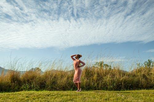 Woman in Pink Bikini Standing on Green Grass Field Under Blue Sky