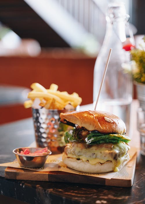 Delicious burger and fried potato on table
