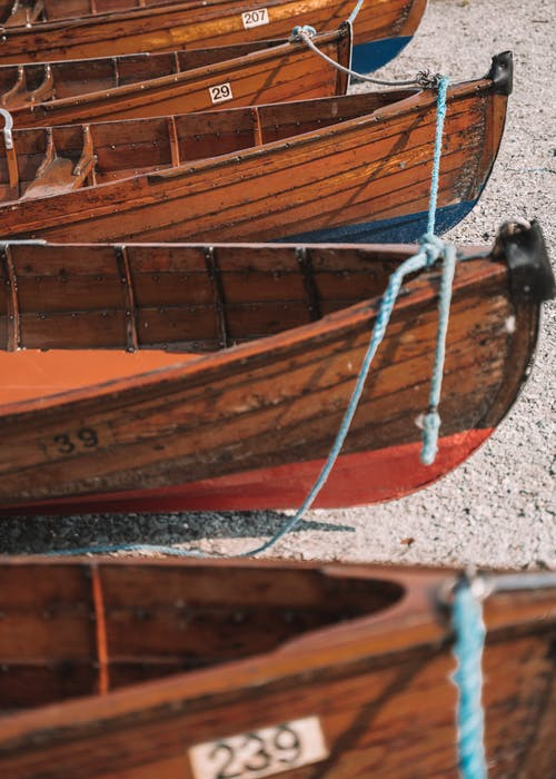 Wooden boats placed on gravel shore