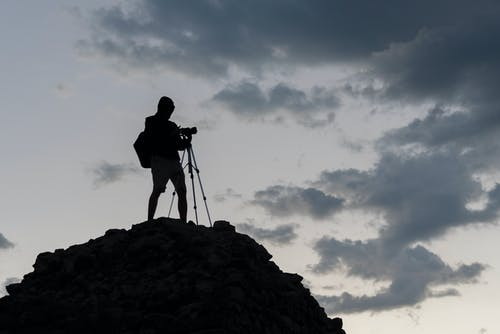 Silhouette of Man Standing on Rocks