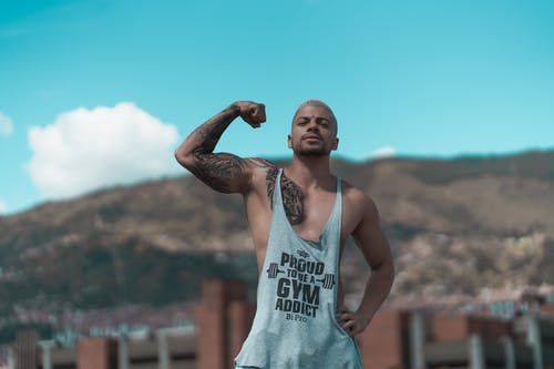 Strong man showing bicep against hilly terrain