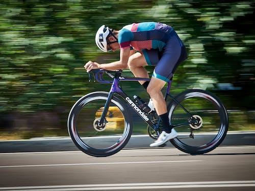 Bicyclist riding bike on asphalt road