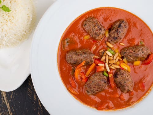 Cooked Meat with Red Sauce on White Ceramic Plate
