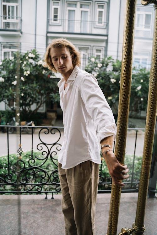 흰 드레스 셔츠와 갈색 나무 울타리에 서있는 갈색 바지에 남자