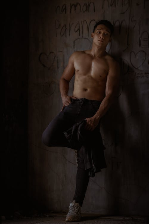 Full body of shirtless male in sporty pants looking at camera while leaning on concrete wall with drawing in abandoned building with hand on hip and leg bent
