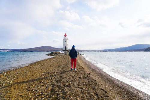 Man in a Hoodie Standing on Brown Sand Near Body of Water