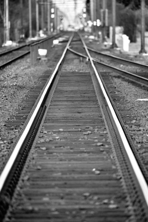 Grayscale Photo of Train Rail