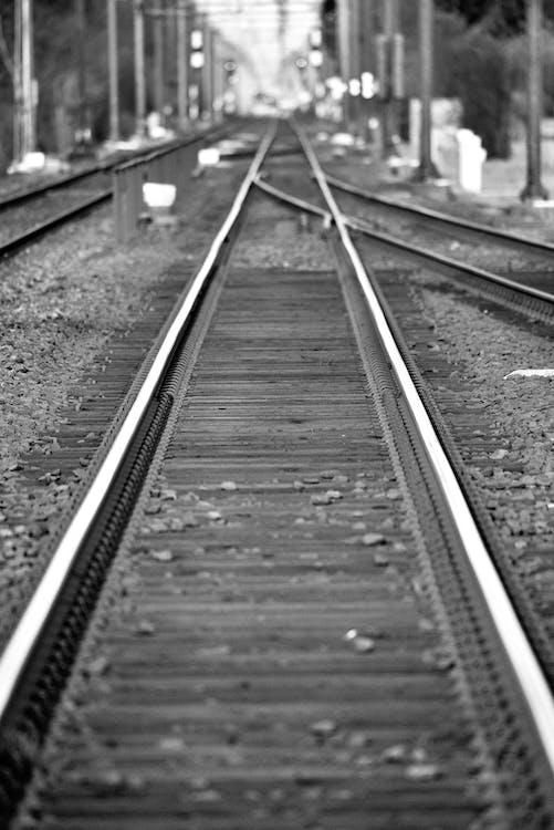 Grayscale Photo of Train Rail