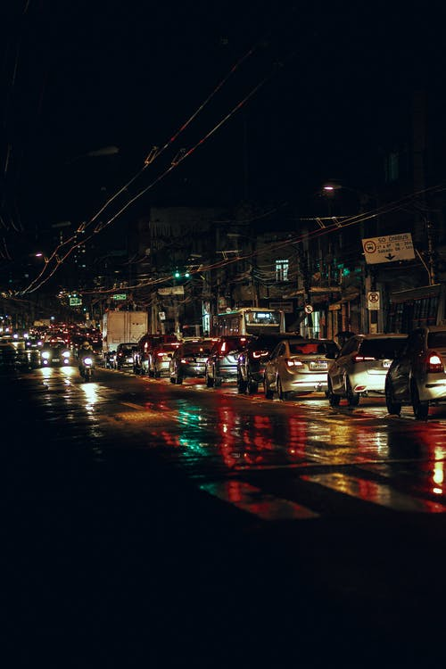 Modern cars with glowing lights in traffic jam on asphalt road on street with buildings and trolley wires at night