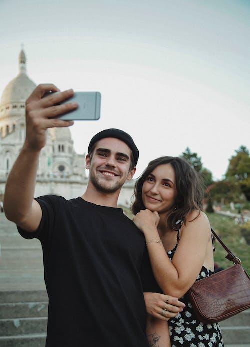 Man in Black Crew Neck Shirt Holding s Smartphone Beside Woman in Black Dress