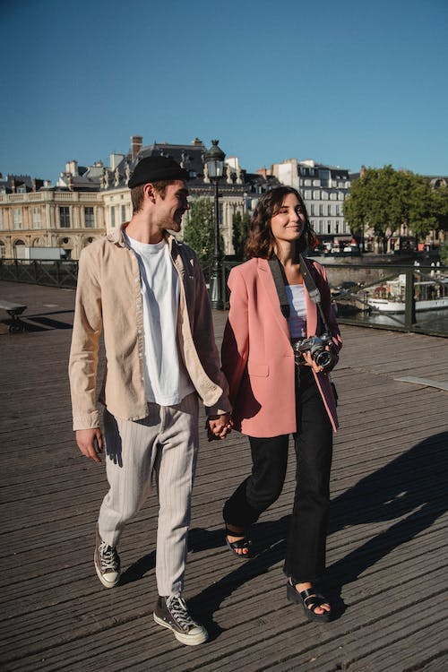 Man in Beige Button Up Shirt and Pants Standing Beside Woman in Pink Blazer