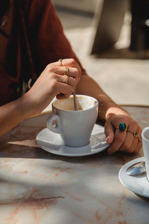 Person Holding White Ceramic Cup on White Ceramic Saucer