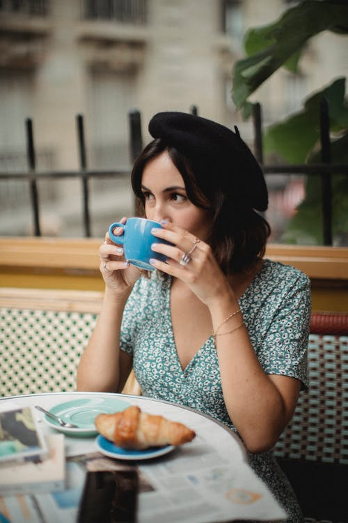 Woman in White and Blue Floral Dress Drinking from Blue Ceramic Mug