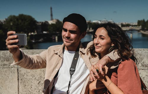 Man's Arm Around Woman's Shoulder While Taking a Selfie