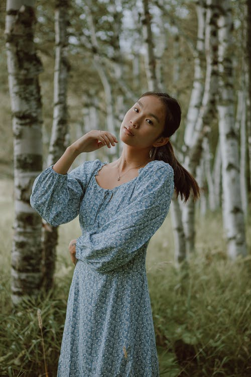 Dreamy Asian female wearing long dress standing among tall trees and grass in woods
