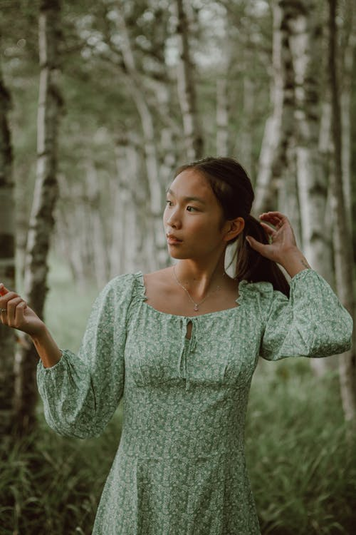 Pensive ethnic woman touching hair while having relaxation in forest