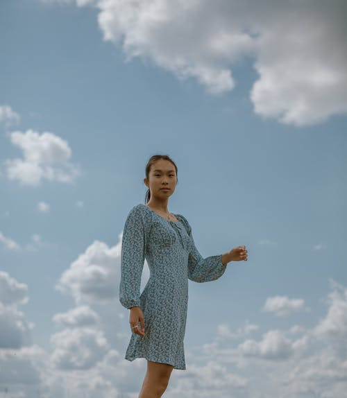 Low angle side view of serious Asian woman in elegant dress standing against cloudy sky
