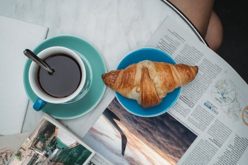 Cup of Coffee Beside a Croissant