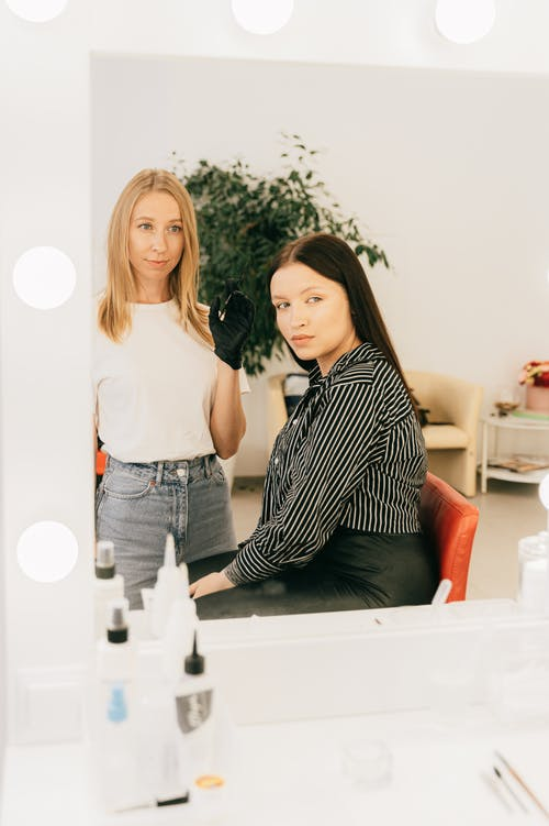 Woman in Black and White Stripe Shirt Beside Woman in White Shirt