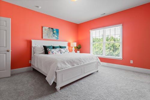 White Bedframe in an Orange Bedroom