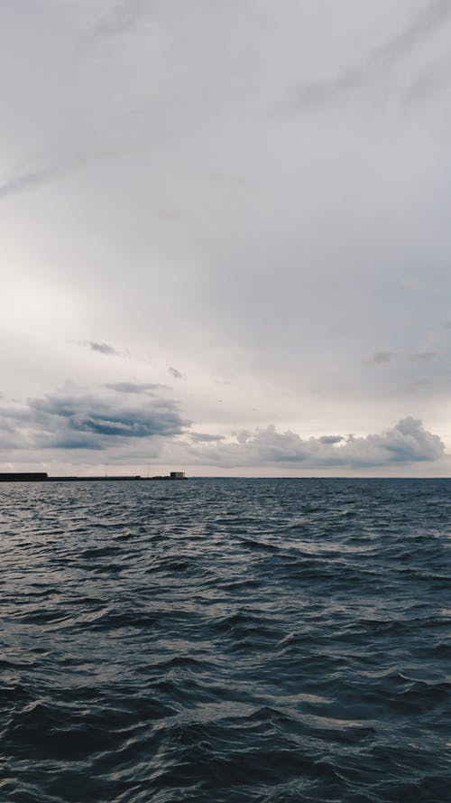 Picturesque seascape of sea with small waves at stormy weather  under cloudy gray sky