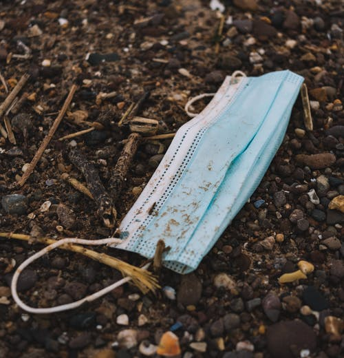 From above of discarded medical mask on rough terrain on street during COVID 19 pandemic